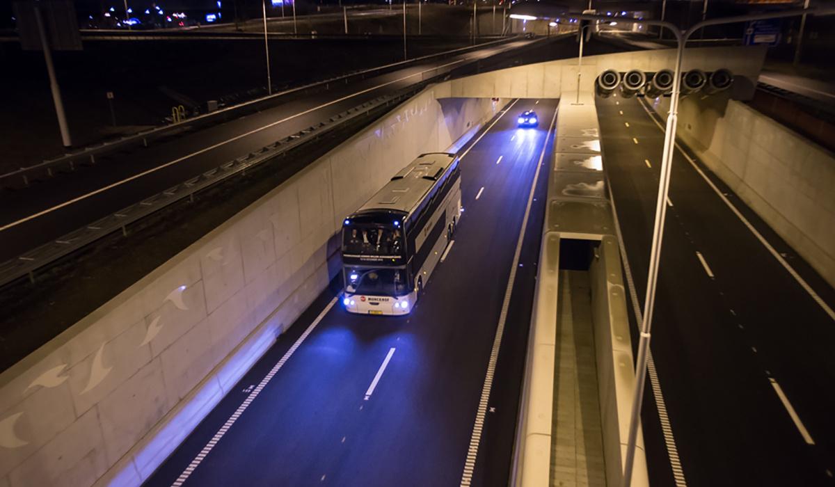 Een dubbeldekker met genodigden gaat als eerste door de tunnel. © Aron Nijss