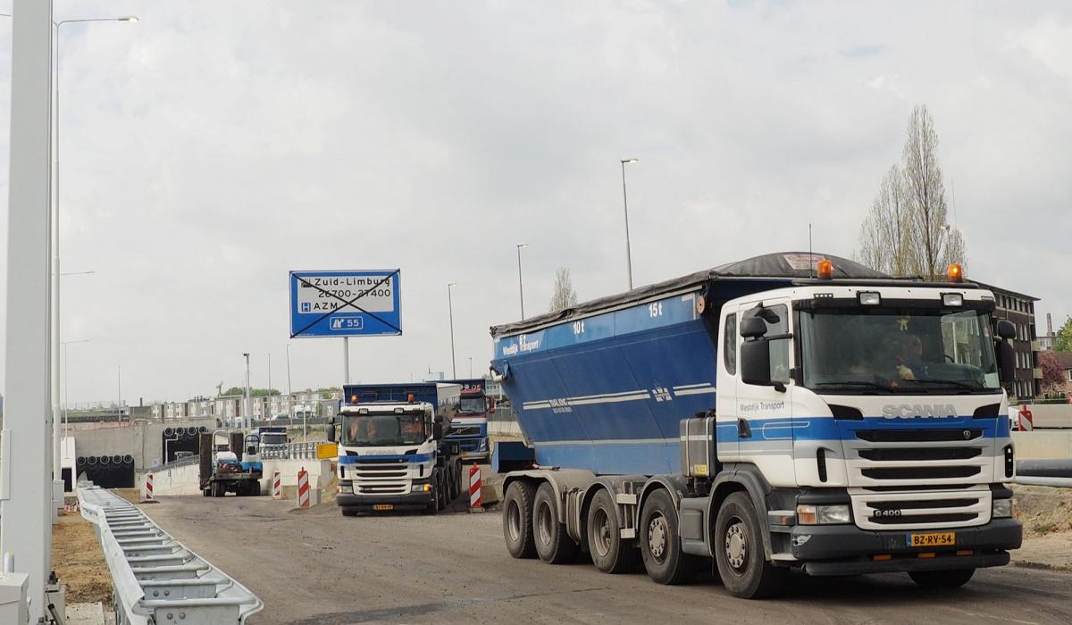 Vrachtwagens met duwbakinstallatie brengen het asfaltmengsel de tunnel in. © Bert Janssen