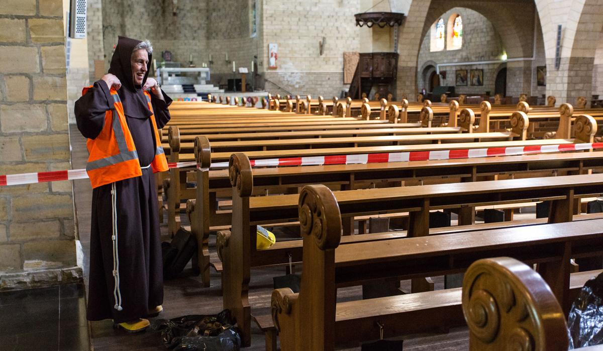 Ook pastoor Jeukens moest veiligheidslaarzen aan in de bouwkuip. © Robert Lambrix